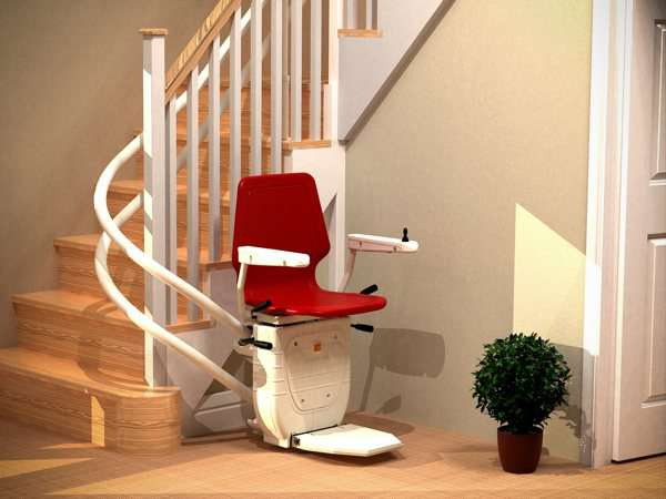 Side angled view of red Dolphin Infinity stair lift parked at bottom of curved stairs with seat, arm rests and foot rest in the down position, showing how the stair lift is parked around the curve, providing easy access to the stairs for people who do not need the stairlift.