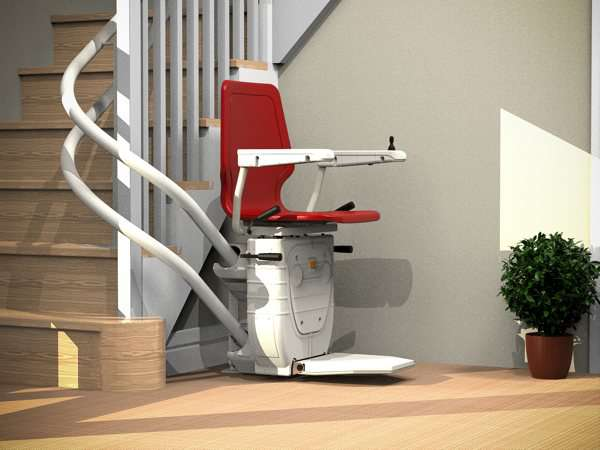 Extreme side view of red Dolphin Infinity stair lift parked at bottom of curved stairs with seat, arm rests and foot rest in the down position, showing how the stair lift is parked around the curve, providing easy access to the stairs for people who do not need the stairlift.