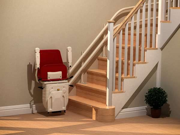 Side angle view of red Dolphin Infinity stair lift parked at bottom of stairs with seat, arm rests and foot rest in up position.