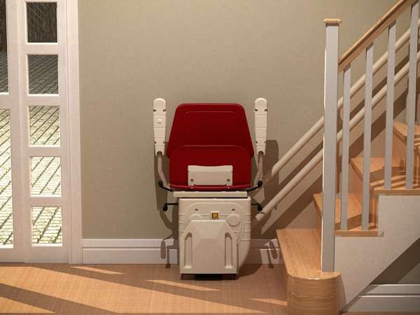 Front view of red Dolphin Infinity stair lift parked at bottom of stairs with seat, arm rests and foot rest in up position.