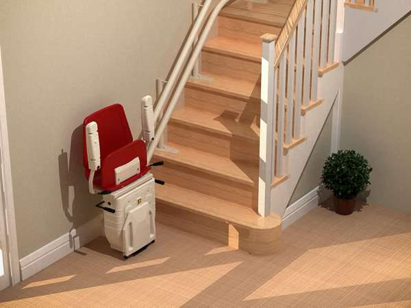 Bird's eye angle view of red Dolphin Infinity stair lift parked at bottom of stairs with seat, arm rests and foot rest in up position.