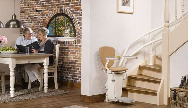 Otolift TWO stair lift with seat parked at the bottom of the stairs. Arm rests and foot rest in the down position.