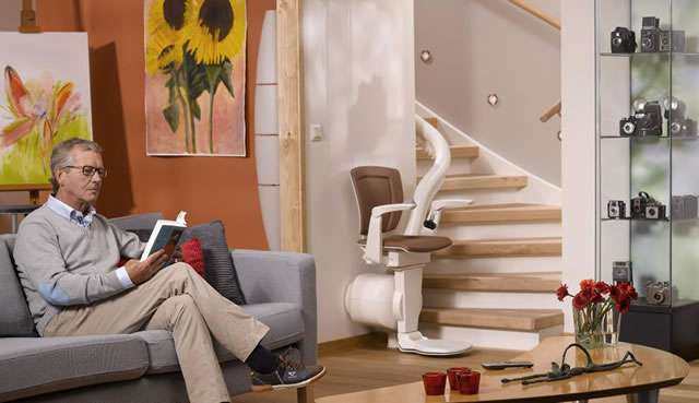 Otolift ONE stair lift parked at bottom of curved stairs. Male user sat on adjacent sofa reading a book.