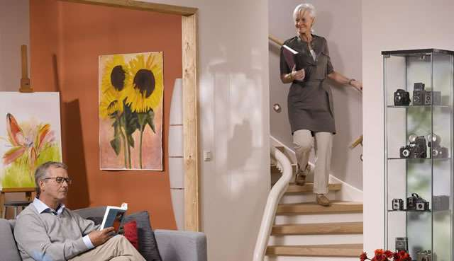 Female user walking down stairs. Otolift stairlift parked upstairs. Male user sat on sofa near bottom of stairs reading a book.