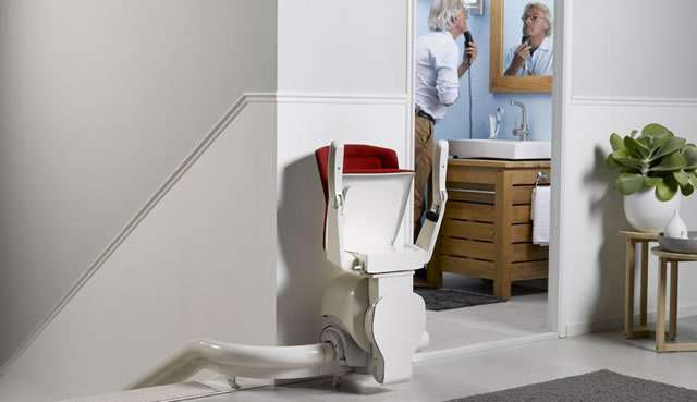 Otolift ONE stairlift parked at top of stairs with seat, armrests and footrest in the up position allowing minimal obstruction at top of stairs landing area.