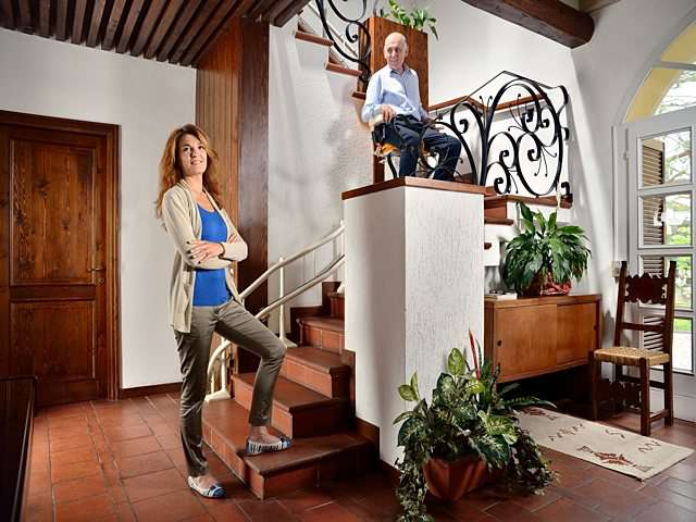 Female user with folded arms standing at bottom of stairs as male user rides Platinum Curve curved stairlift chair up the stairs.