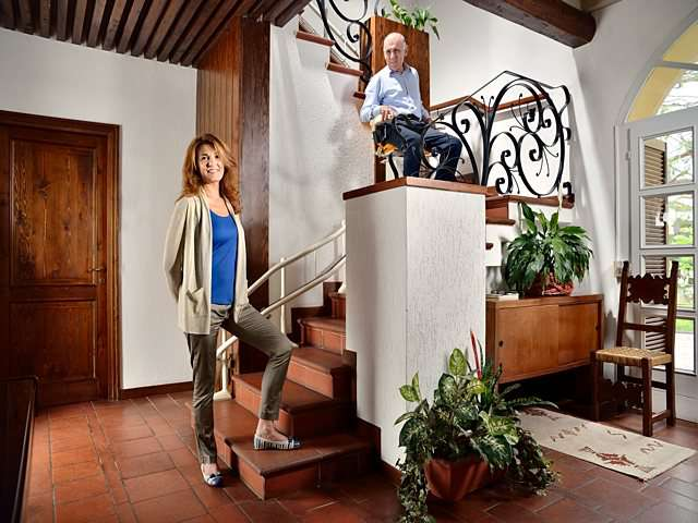 Female user standing at bottom of stairs as male user rides Platinum Curve curved stairlift chair up the stairs.