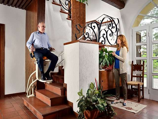 Male user rides Platinum Curve curved stairlift chair down the stairs.