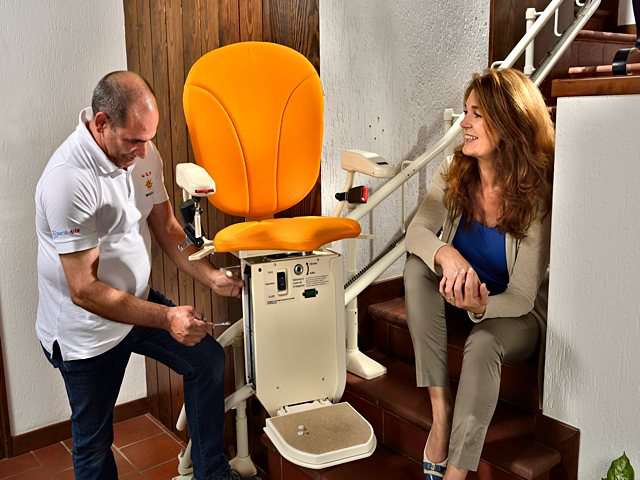 At bottom of stairs, stairlift installation engineer making final adjustments to Platinum Curve stairlift. Female stairlift owner sitting on stairs talking with stairlift engineer.