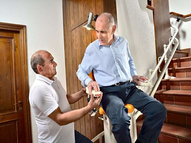 Male user is sat on the chair of the Platinum Curve stairlift at the bottom of the stairs, as the stair lift installation engineer makes final adjustments to the chair lift mechanism.