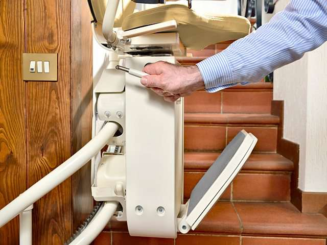 The male user adjusting the chair swivel arm of the Platinum Curve stair lift.