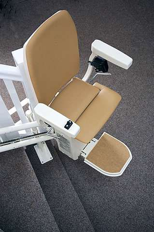 Platinum curved stair lift, gallery image 02 of 8. Tan-coloured upholstery stairlift parked at bottom of stairs, with seat, footrest, and arm rests in down position, stair lift ready to use.