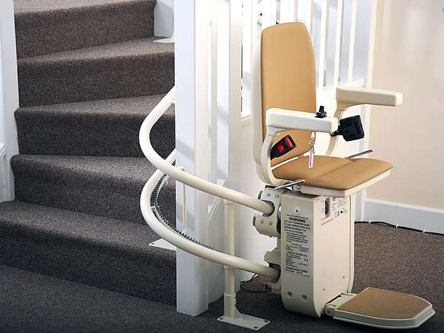 Platinum curved stair lift, gallery image 04 of 8. Tan-coloured upholstery stairlift parked at bottom of stairs around the curve, with seat, footrest, and arm rests in down position, in parked state.