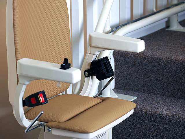 Platinum curved stair lift, gallery image 06 of 8. Tan-coloured upholstery stairlift parked at bottom of stairs, with seat, footrest, and arm rests in down position, angled view.