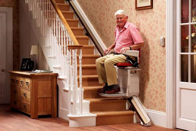 Smiling male user is sat on the Stannah Saxon 420 stairlift with seatbelt on and is either riding up the straight stairs, or riding down the stairs.