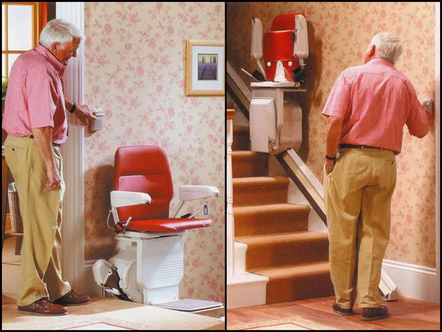 A 2-part composite image of the Stannah Saxon 420 stairlift. The left side image shows a male user standing at the top of the stairs pressing a button on a wall-mounted wireless remote control, while watching the Saxon 420 stairlift at the top of the stairs. The right side image shows the same male user standing at the bottom of the straight stairs pressing a button on another wall-mounted wireless remote control, as the Stannah Saxon 420 stair lift with red upholstery is shown mid-way up the stairs with the arm rests, seat, and foot rest all in the up position.