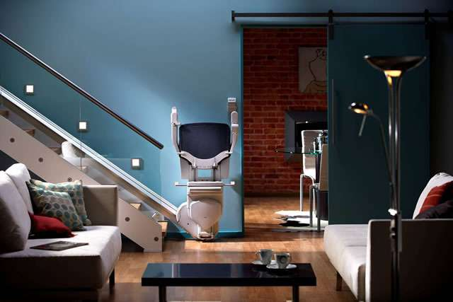 A front facing photo of a dark blue coloured Stannah Solus 420 stairlift shown parked at the bottom of the straight stairs, with seat, armrests, and footrest all in the up position.
