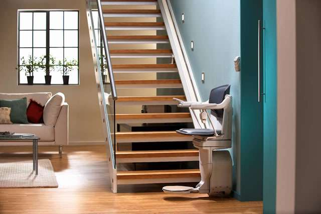 A full side view photo of the Stannah Solust 420 stair lift parked at the bottom of the straight stairs. The armrests, seat, and footrest are all in the down position, so the stair lift is ready for use.