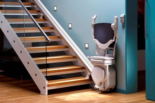 A front-to-side angle photo of the Stannah Solust 420 stair lift parked at the bottom of the straight stairs, with the stairlift chair swivelled to face the camera. The armrests, seat, and footrest are all in the up position, showing how much extra walking space is therefore made available, when the stairlift usage is not required.