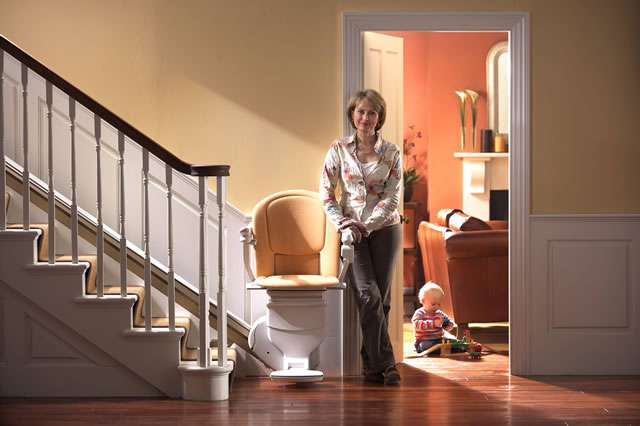 A front view of smiling female user standing next to a tan-coloured Stannah Sofia 420 stair lift parked at the bottom of straight stairs. The stairlift arm rests, seat, and foot rest are all in the down position.