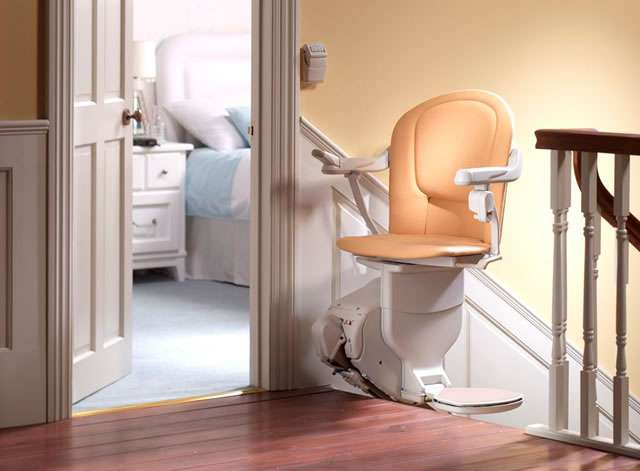 A tan-coloured Stannah 420 stairlift parked at the top of the straight stairs and facing the landing area, providing a safety barrier across the stairs.