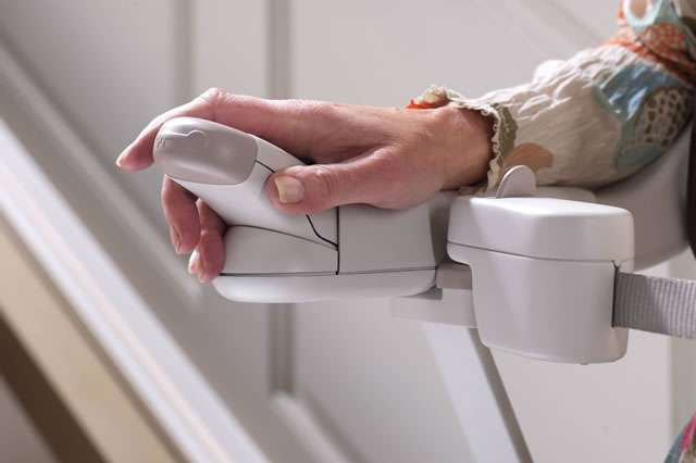 A close-up photo of female user operating the armrest controls of a Stannah Sofia 420 stairlift.