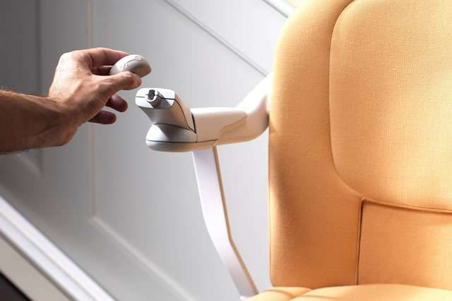 A front view close-up photo of the hand of female user removing the front of the armrest keylock toggle from its socket area on the Stannah Sofia 420 stair lift.