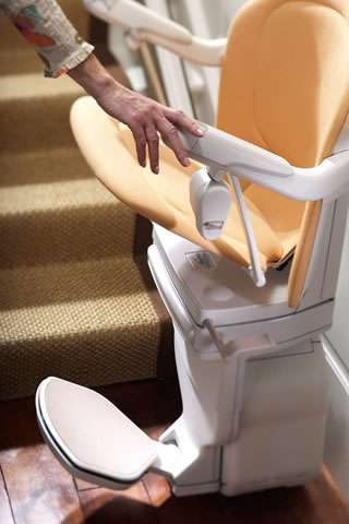 A close-up mostly side angled view of a tan coloured Stannah Sofia 420 stairlift, illustrating the interlinked nature of the seat, armrests and footrest. As the seat is moved up or down, the arm rests and foot rest also move the same direction.