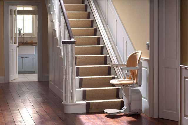 A mostly side angle view of a tan-coloured Stannah Sofia 420 stair lift parked at the bottom of straight stairs. The stairlift arm rests, seat, and foot rest are all in the down position.