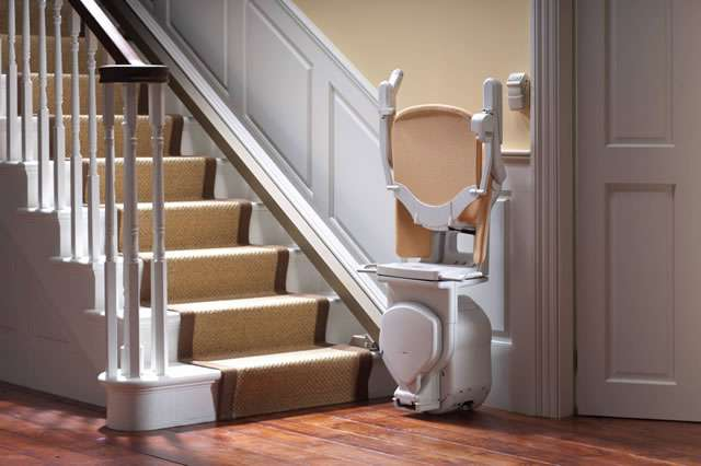 A mostly side angle view of a tan-coloured Stannah Sofia 420 stair lift parked at the bottom of straight stairs. The stairlift arm rests, seat, and foot rest are all in the up position.