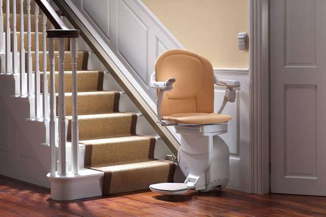 A mostly front angle view of a tan-coloured Stannah Sofia 420 stair lift parked at the bottom of straight stairs, facing away from the stairs. The stairlift arm rests, seat, and foot rest are all in the down position.