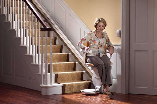From a mostly front angle view, a smiling female user sitting on a of a tan-coloured Stannah Sofia 420 stair lift parked at the bottom of straight stairs, facing away from the stairs.