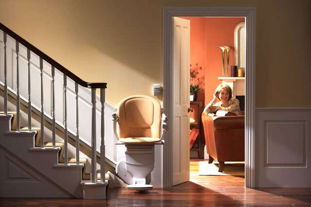 A front view of a tan-coloured Stannah Sofia 420 stair lift parked at the bottom of straight stairs. The stairlift arm rests, seat, and foot rest are all in the down position. In the background, through an open doorway, a smiling female user looks at the stairlift area and camera.
