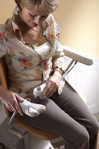 A close-up photo of a smiling female user sitting on a Stannah Sofia 420 stairlift, and putting the seatbelt on.