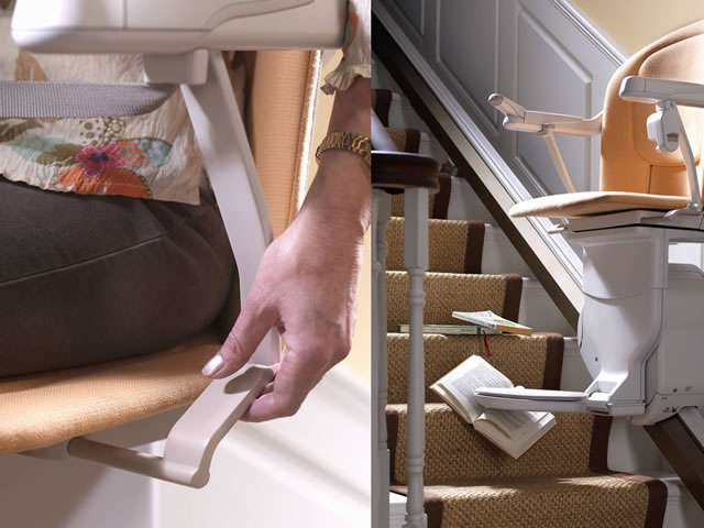 A close-up view of a female user's arm and hand operating the swivel lever underneath the seat of a Stannah Sofia 420 stairlift.