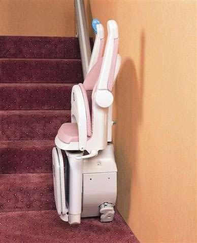 A side view photo of a Handicare 1000 series pink coloured stairlift parked at the bottom of the stairs, with the armrests, seat, and footrest all in the up position.