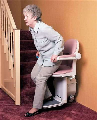 A female user about to sit on, or about to stand up from, a pink coloured Handicare 1000 series stairlift parked at the bottom of the stairs.