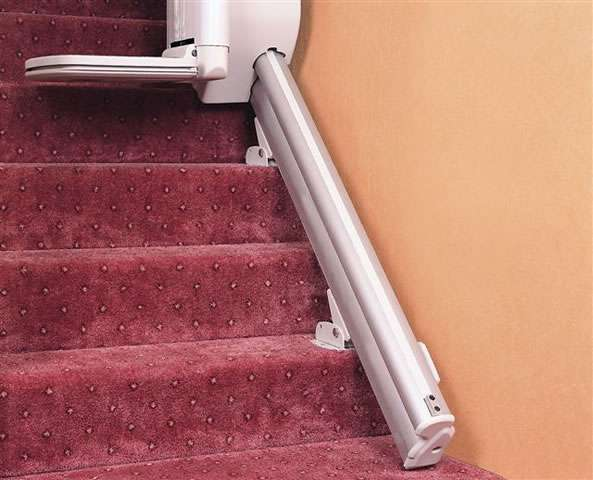 A close-up photo of how neatly a Handicare 1000 series stairlift rail fits to the floor.