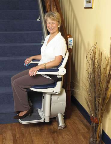 A side view photo of a smiling female user sitting on a blue coloured Handicare 1000 series stair lift parked at the bottom of a straight staircase, with armrests, seat, and footrest all in the down position, and seatbelt on.