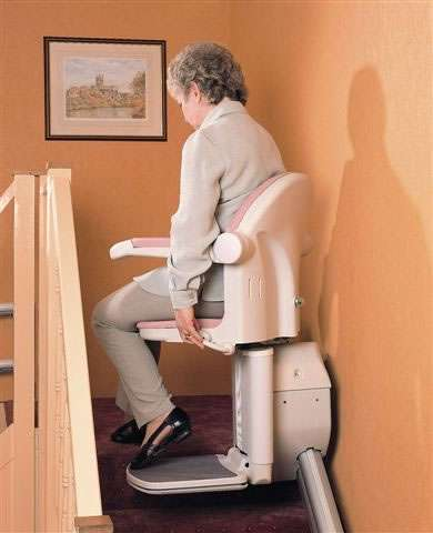 A side view of a female user sitting on a Handicare 1000 series stairlift as it arrives at the top-of-stairs landing area, and the user is starting to swivel the chair to face the landing area.