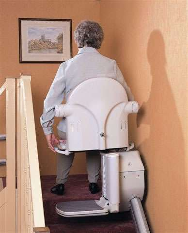 A side view of a female user sitting on a Handicare 1000 series stairlift as it arrives at the top-of-stairs landing area, and the user has fully swivelled the chair to face the landing area. So the user can now safely step off the chair and continue her journey.
