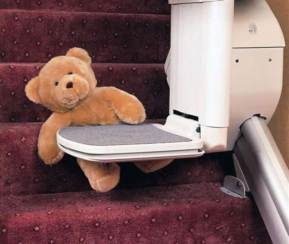 A Handicare 1000 series stairlift as it travels up and down the stairs. A close-up photo of what happens when the footrest touches an obstacle, such as a child's teddy bear, in its path. The stair lift movement pauses to allow someone to remove the obstacle on the stairs.