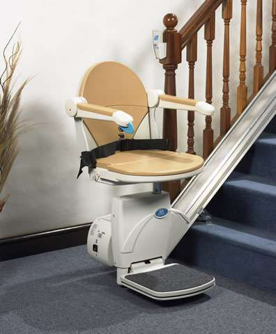An opposite angled front-to-side view of beige-coloured Handicare Simplicity 950 stair lift parked at the bottom of straight stairs, with armrests, seat, and footrest all in the down position, so the stairlift is ready to use.