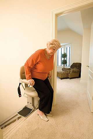 Female user about to get off a Homeadapt Elite stair lift after travelling up the stairs.