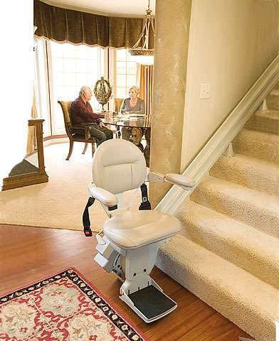 A Homeadapt Elite stair lift parked at the bottom of straight stairs, with the arm rests, seat, and foot rest all in the down position, ready to use the stairlift.