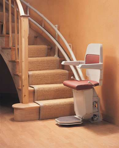 The Stannah Sarum 260 curved stair lift in red shown parked at the bottom of the stairs. The arm rests, seat, and foot rest are all shown in the down position, ready to use.