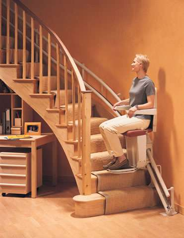 Photo of smiling female user riding up curved stairs on a red colour upholstery Stannah Sarum 260 series stairlift/