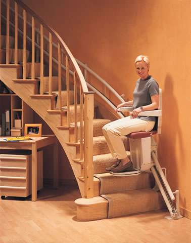 Smiling female user is riding on the Stannah Sarum 260 series stair lift up or down the curved stairs.