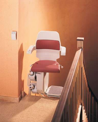 The Stannah Sarum 260 series stairlift is shown parked at the top of the stairs, with the chair facing inwards to the landing.