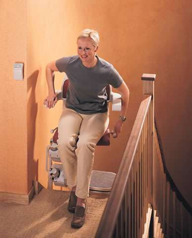 A female user is about to sit on the Stannah Sarum 260 red stairlift that is parked at the top of the stairs with the stair lift chair facing inwards to the landing.